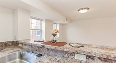 The Oaks Apartments | Southeast Washington, DC | Affordable Apartments in DC | Anacostia Neighborhood | Granite Covered Counters | Laminate Wood Flooring | Renovated Community | Kitchen Overlooking Living Room |