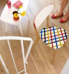 l'assise d'une chaise en bois blanc est customisée avec des bandes de ruban adhésif rouge, jaune, bleu et noir, placées en écossais.
