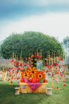 Beautiful mehendi setup under a tree with colourful tassels | WedMeGood|#wedmegood #indianweddings #indiandecor #decorideas #tassels #tasseldecor #mehendidecor #mehendiseats