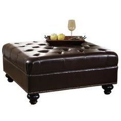 "Button-tufted cocktail ottoman with bi-cast leather upholstery and wood frame. Product: Cocktail ottoman    Construction Material: Hardwood, bi-cast leather and high density foam     Color: Dark brown Features: Tufted    Dimensions: 18"" H x 38"" W x 38"" D"
