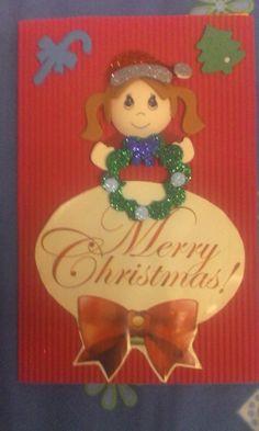 Tarjeta navideña hecha con papel corrugado y unos adornitos