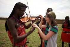 She was teaching this guy how to play the violin in Africa