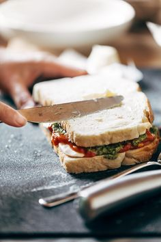 Caprese Grilled Cheese: loaded with basil pesto, a thick and chunky garlic butter tomato sauce, and fresh mozzarella cheese, all on grilled sourdough bread. The literal taste of summer. | pinchofyum.com