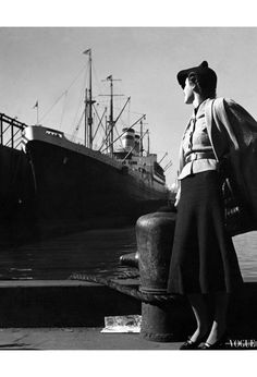 Model, standing at a port with the ocean liner Hansa in the background, wearing a wool mesh cape over a belted jacket, dark blouse and skirt, and holding a black alligator bag by Koret, Vogue december 1936. Photo Toni Frissell