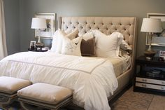 Upholstered headboard, mirrors instead of pics behind lamps, footstools at end of bed #bedroom