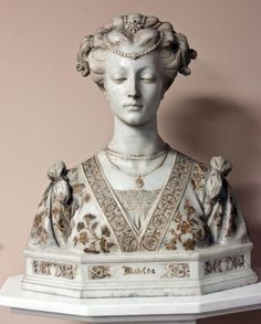 """Large marble bust of a woman in affluent garb. Beaded pearl head dress. Has carved floral decoration and is gilded. Front of bust has """"Matelda"""" etched and gilded. No apparent signature. 19th Century. White marble pedestal has a design to top that matches the shape of the base of the bust. Bust of woman, 19th century"""