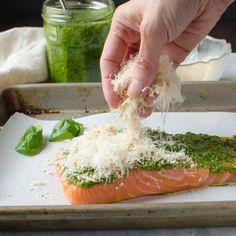 sprinkling parmesan breadcrumbs on salmon pesto recipe for a 4 ingredient meal.
