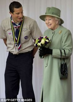Britain's Queen Elizabeth II speaks with Chief Scout, Bear Grylls during the review of Queen's Scouts at Windsor Castle in Windsor in April 2012
