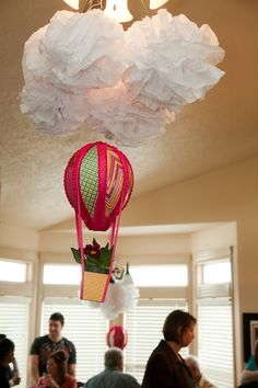 Cover our chandelier with white paper and puff balls and hand hot air balloons from the bottom slats