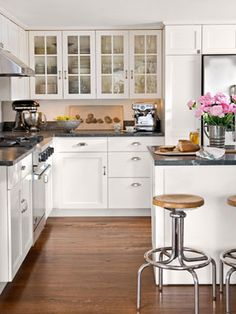 Soapstone counters, vintage lab stools, and a bank of whitewashed wooden cabinets add to the warmth of an already sunny kitchen.