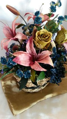 This lovely silk upscale arrangement comes in a beautiful wicker basket with navy blue and tan embellishments weaved into the basket . Four large mauve rose stargazer lily stems, three large green rose stems, 2 navy hydrangea stems, navy spray roses through out arrangement. Lots of miscellaneous purple and brown stems to enhance the beautiful arrangement and make it pop. Lots of beautiful upscale greens making sure the floral arrangement is full and lush.  All of my silk floral stems are…