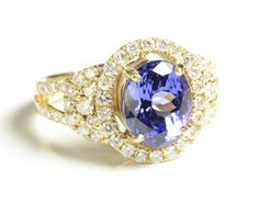 TANZANITE, DIAMOND AND FOURTEEN KARAT GOLD RING, with round-cut diamonds set around an oval-cut tanzanite weighing approximately 2.87 cts. Ring size: 7-1/4.   Lot 1213-0686.