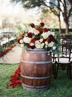 Wine barrels topped with jewel-tone flower arrangements mark the entrance of the wedding ceremony site | DFW Events | Photo: Sarah Kate, Photographer | Floral: Stems of Dallas