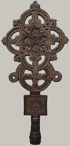 "Processional Cross, 16th century, Eithiopia. ""This cross was created in the province of Tigray, near the Red Sea, the birthplace of Ethiopia's earliest kingdom and of Christianity in Africa.  Underlying this exceptional object's aesthetic is a technically accomplished fusion of wood sculpture and metalwork..."""