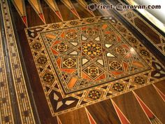 Close up at the design in the center of the backgammon table, featuring a flower-like pattern with colorful elements, including the beautiful orange reddish rosewood and luxurious inlaid mother-of-pearl