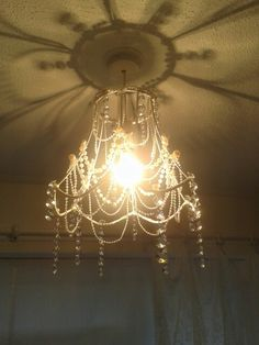 My homemade chandelier using strings of pearls, crystals and an old lampshade frame Fixed together with my glue gun ! Cheap and cheerful !
