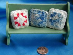 Dollhouse miniature bench with crocheted pillows.