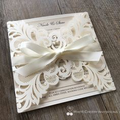 Laser cut wedding invitation by White Cherry Invitations layered with ivory metallic card stock and tied off with an ivory satin ribbon. Accompanied with a metallic ivory 160mm x 160mm envelope.