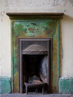 A metal grate & interior surrounded by green all w/ a vintage look. This small fireplace is one-of-a-kind!