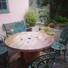 Once an unwanted wire reel left out in the rain, now a classy centre piece perfect for any patio or courtyard type place. With the combination of varnish and black Hamerite this table is an all year round table so you don't need to find anywhere dry for it over the wetter months! There is a little door on the side that can be used to put things inside keeping them cool or dry. http://reveloce.wordpress.com/rustic-garden/