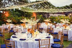 Light canopy, orange uplighting, chiavari chairs, specialty napkins and chair cushions in royal blue, standard white linens, floral centerpieces from Flowers by Heidi, Four Seasons Resort Hualalai Weddings