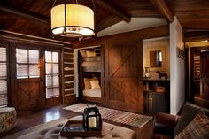 """This family room has a creative bunk-bed with a large """"barn door"""" that slides over the dresser when the beds are in use and hides the beds during the day"""
