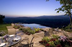 Stunning hillside view from this patio area with infinity pool and patio in natural slate tile by AMS Landscape Design Studios in Newport Beach, CA.