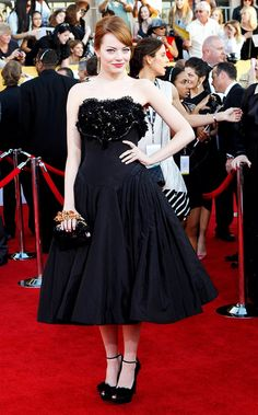 Emma Stone in a black strapless, tea-length Alexandra McQueen dress, clutch and shoes