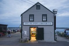 Diners flank both sides of the Five Islands Lobster Co. shack at dusk.
