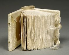 Pamela Spitzmueller.  twelfth-century style with exaggerated tongue corners; edge sewn cap tabs; clasps of wide tawed straps with tassles on a brass fore edge peg. 13 x 10 x 8 centimeters. Created 1995.