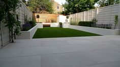 Modern London garden design, smooth sawn beige sandstone paving, raised block paving walls, hardwood privacy screen trellis, balau hardwood floating bench, block architectural planting.