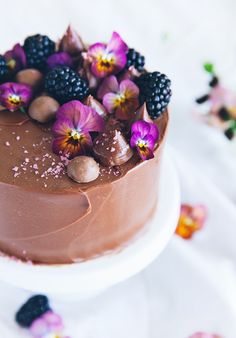 Chocolate and Nutella vertical roll cake with fruit and edible flowers by Call Me Cupcake.