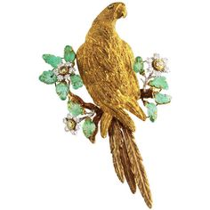 BUCCELLATI - 1960s 18k Yellow Gold, Diamond, Colored Diamond and Emerald Bird Brooch.  Designed as a Parrot perched upon a branch surround by flowering plants, the eye bezel-set with a round green Diamond  (approx. 0.02 ct), the Rhodium plated vines set with 11 carved Emerald leaves, the flowers set in the centers with 3 Diamonds of brownish yellow color (approx. 0.65 ct), the petals set with 18 round Diamonds (approx. 0.60  ct.) Signed Gm Buccellati, Italy, Stamped 18K.