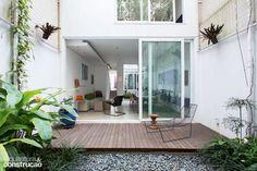 O declive do terreno foi aproveitado no projeto: um pequeno lance de escadas dá acesso à sala, com pé-direito mais alto do que o do restante da morada. | <i>Crédito: André Klotz