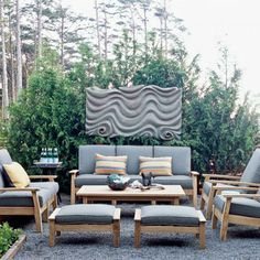 Pea gravel creates the illusion of an area rug on this modern patio. A dramatic sculpture creates a focal point and lends interest to this outdoor living room. coastalliving.com