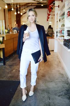 Black blazer draped over the shoulder, white t-shirt, and white cuffed jeans