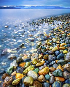 A view of a colorful, rocky shoreline along the Puget Sound in Washington State. View is from Lincoln Park in West Seattle looking out across the water towards the Olympic Mountains.