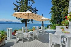 Luxury deck with white outdoor furniture and waterfront views