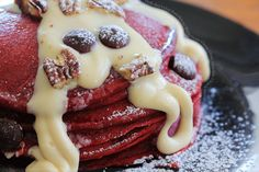 Fluffy red velvet pancakes with maple cream cheese glaze chocolate chips and pecans via foodporndaily.com