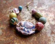 Lotus Gem… These hand formed, hand carved ceramic beads and lotus gem link are glazed in shades of the ocean and love. This set and its beads are an original copyright protected design. © 2015 Gaea Cannaday