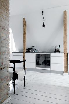 Love the natural wood beam and the modern kitchen