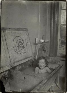 PERSONAL CARE, CHILDREN: Taking a bath. 1908 - Notice the lid on the tub. The tub has two sinks. Baby is washed in one; clothes in the other. But, baby is wearing a shirt of sorts.