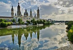 Sunlight breaks through the clouds over the River Ebro and the Basílica del Pilar in Zaragoza.