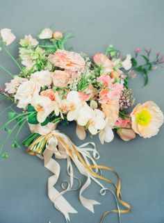 Exquisite post of blooms including jasmine and roses with poppies and orchids and thin trailing ribbons. Now this is how to photograph a posy!