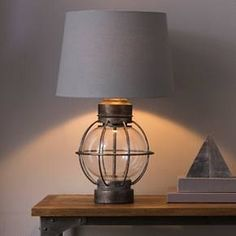 • Metal and glass<br>• Inspired by railroad lanterns<br><br>The Railway Table Lamp in Grey from Beekman 1802 FarmHouse was inspired by the railway line that used to run between New York City and Sharon Springs, NY. The lamp has classic appeal but fits marvelously in a modern setting.