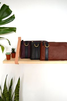 I made this simple shelf for our product shots in a flash! Two strips of Veg Tan leather cut 1in wide and 24in long, 4 nails, wood board cut to desired length. LOVE IT!