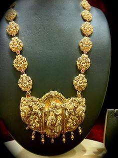 Heavy Nakshi haram with Radha Krishna pendant studded with rubies by Nalli Jewellers, Chennai.