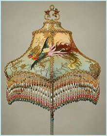 """ORNATELY HAND PAINTED ANTIQUE BASE WITH A JEWELED PULL CHAIN HOLDS A""""FLYING PHOENIX CHINOISERIE"""" SHADE WITH COLORFUL ANTIQUE CHINESE PHOENIX APPLIQUES WRAPPED AROUND IT. THE SHADE IS DYED PALE GOLD TO CELADON GREEN AND COVERED IN GOLD METALLIC LACE AND MESH. THE TOP PANELS ARE COVERED IN A BEAUTIFUL PASTEL LAME AND METALLIC LAME FROM PARIS. COLORFUL HAND BEADED FRINGE IN  MATCHING COLORS ADORNS THE BOTTOM"""