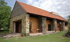 K přestavbě stodoly na obytný dům pro čtyřčlennou rodinu přistoupili architekti neobvyklým způsobem. Do 150 let staré kamenné konstrukce vložili montovanou dřevostavbu.