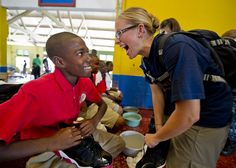 Kari Williams, Continuing Promise 2011 international program director for education, gives a new pair of shoes to a student during a Continuing Promise community service project at the Alpha Boys School.
